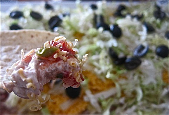 This easy taco dip takes only minutes to make. It is a perfect dish for a tailgate party, game day, potluck, or any kind of get together. #WomenLivingWell #gamedayfood #taco #easyrecipes